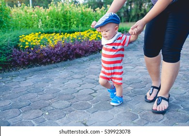 First steps of little adorable Asian toddler boy wearing hat among beautiful and colorful flower garden in public park of Thailand, Happy and cute baby learning to walk with mother, mother day concept