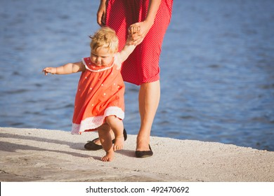 first steps of little girl with mother