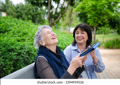 The first successes in the use of tablet cause joyful feelings and positive emotions of an elderly woman.