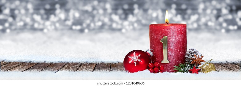 first sunday of advent red candle with golden metal number one on wooden planks in snow front of silver panorama bokeh background