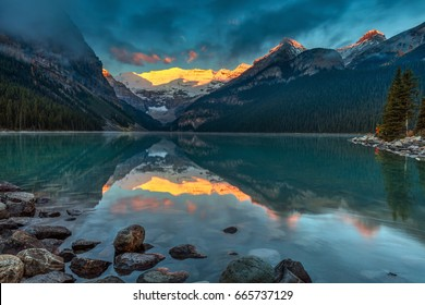The First sunlight illuminating Victoria glacier on a calm morning in Autumn at Lake Louise in Banff National Park, Alberta, Canada.