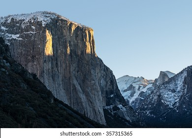 First sunlight streaking across El Capitan during a winter sunrise.  Snow capped Clouds Rest and Half Dome are also visible.
