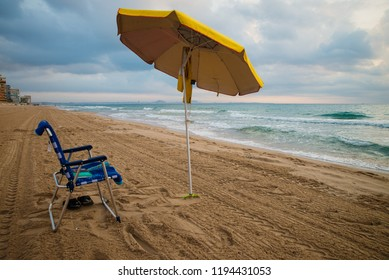 First sunshade planted on a Mediterranean beach in the early hours of the morning