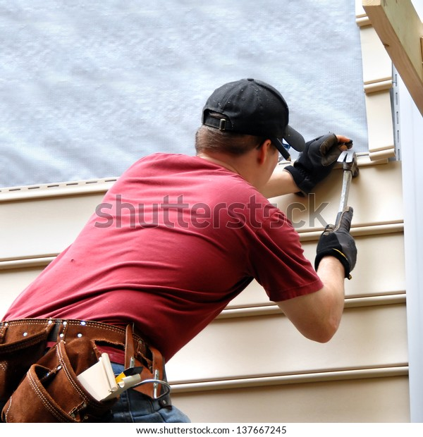 First time home buyer works to install siding on his new home.  He is hammering into place a sheet of siding.  He has on a red shirt and is holding hammer and nail.