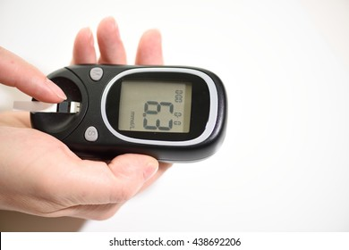 First type Diabetes patient measuring glucose level blood test use glucometer and small drop of blood from finger and test strips