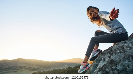 first view of woman hiker with backpack sitting on edge of cliff against background of sunrise and extends a hand