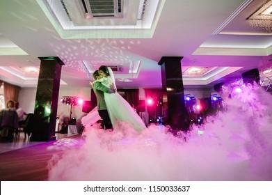 First wedding dance of newlywed. bride and groom dancing in restaurant. Wedding couple dancing in smoke.