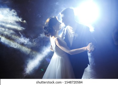 First wedding dance of newlywed. Wedding couple dancing in the darkness. Groom holds bride's hand dancing with her in the middle of a restaurant. Happy bride and groom and their first dance.