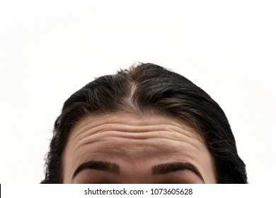 First wrinkles. Girl with wrinkles on forehead. Portrait of young woman with wrinkles on his forehead on white background. Do I have wrinkles? Woman looks in the mirror