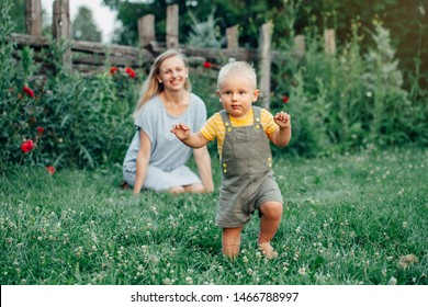 First year child milestone. Baby toddler one year old making his first steps. Caucasian mother watching her son boy walking outside in park on grass on summer day. Happy family lifestyle.