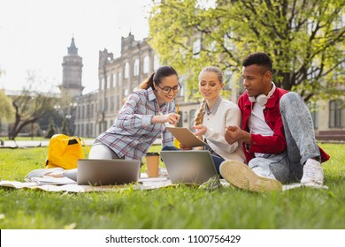 First year. First year students feeling curious while looking at their university schedule sitting outside