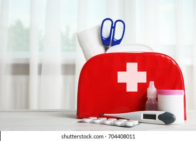 First-aid kit and medicines on the table in the background of the window.