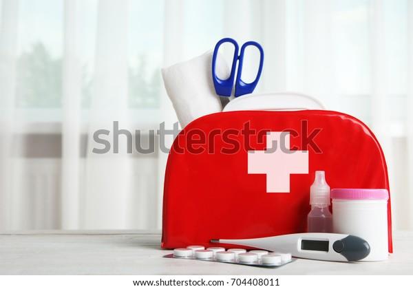EHBO-kit en medicijnen op de tafel op de achtergrond van het venster.
