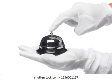 First-class service. Hand in white gloves holding hotel bell