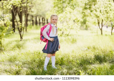 first-grader girl stands with a school pink backpack in full length outdoors