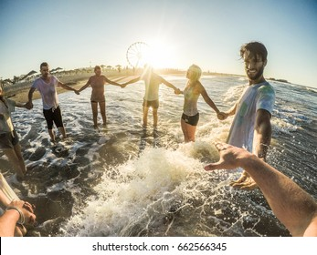 Firsthand view of happy friends having fun on the beach at sunset - Young people playing inside sea water outdoor - Friendship, youth,travel concept - Soft focus on right man face - Contrast filter