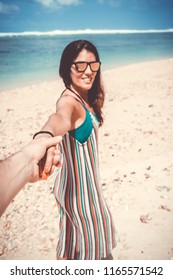 Firsthand view of young woman having fun on the beach at sunset. Focus on woman hand