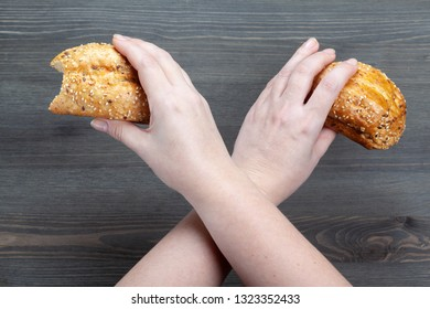 First-person view of the bitten bread in crossed arms at dark wooden background. Dietary concept. Copy space