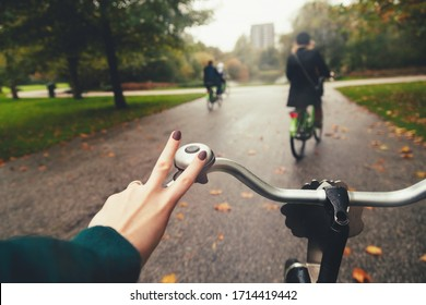 First-person view of cyclist. Group of friends riding bicycles in rainy autumn park. Rider's hand in on a bicycle handlebar. Healthy lifestyle