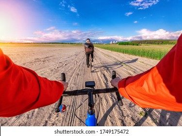 First-person view of a cyclist on a blue gravel bike riding on a sandy field with a friend. The versatility concept of gravel bicycles.