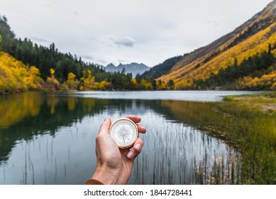 First-person view of a female hand with a compass on a background of a beautiful mountain landscape. The concept of navigating the search for your own path and orientation to the cardinal points