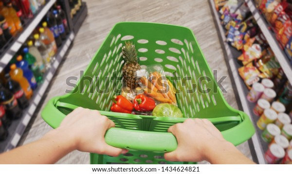 First-person view of female hands moving shopping trolley with fresh colorful vegetables and fruits through aisles of supermarket, sale and shopping concept
