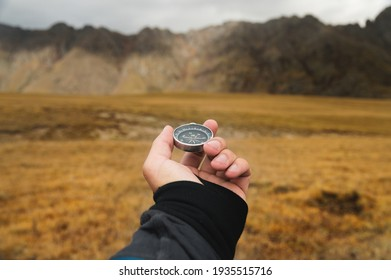 First-person view of a male traveler s hand holding a magnetic compass against the backdrop of a mountainous area. Orientation and finding your way