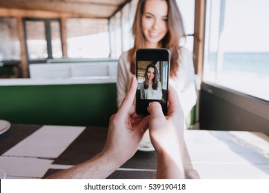 First-person view of man making photo on phone his smiling woman on date in cafe near the sea