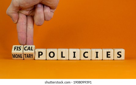 Fiscal or monetary policies symbol. Businessman turns wooden cubes, changes words fiscal policies to monetary policies. Orange background. Business and Fiscal or monetary policies concept. Copy space.