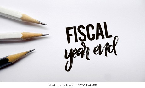 Fiscal year end memo written on a white background with pencils