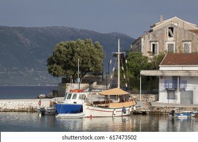 FISCARDO, GREECE- April 29, 2016: The village of Fiskardo with its calm blue bay and houses. Two boats anchored by the promenade of the village.