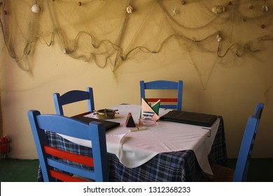 Fiscardo, Kefalonia, Greece - June, 3: Detail of the interior of the restaurant. Greek restaurant, chairs, tables, network. Empty wooden blue table and chairs. June, 3 2015
