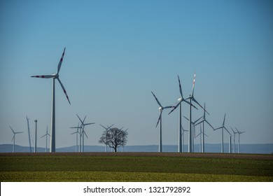FISCHAMEND/ AUSTRIA FEB 2019: Eco power. Wind turbines generating electricity. Green environment. Spring sunny day on green field with wind power generators in Austria