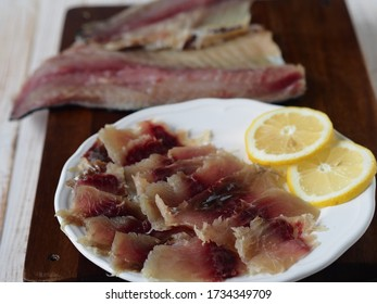 Fish background. Balyk pieces from freshly salted Russian river fish on the background of fish carcasses on the kitchen cutting Board on a white wooden table.