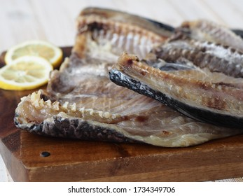 Fish background. Carcasses of freshly salted Russian river fish, ready to eat, on the kitchen cutting Board on a white wooden table.