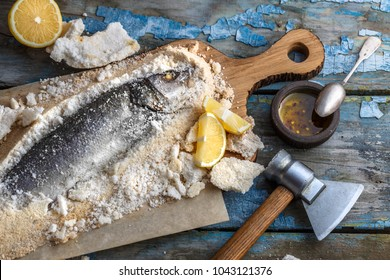 Fish baked in salt with lemon and oil, top view