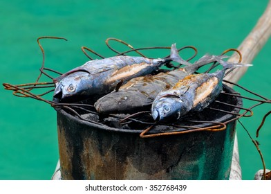 Fish barbecue on a grill top of barrel in wooden boat in front of turquoise water