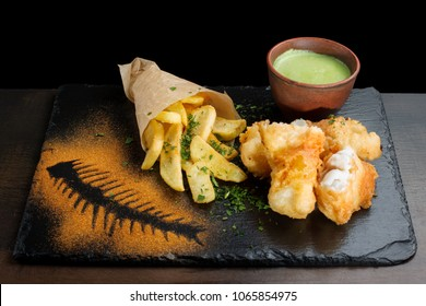 Fish in batter, French fries. The sauce is in a clay pial, all laid out on a black slate.