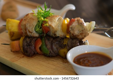 Fish and beef barbecue with tomato and bell pepper on wooden skewers