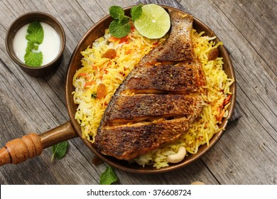 Fish Biryani -Popular Indian dish made of fish marinated with Indian spices fresh herbs and cooked with Basmati rice