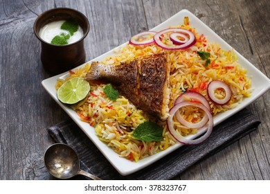 Fish Biryani - Popular Indian dish made of fish marinated with spices and slowly cooked with Basmati rice, selective focus