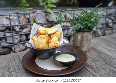 Fish bites battered with homemade tartar sauce served on wooden table in a garden