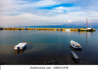 Fish boats in Oropos marina, Attica, Greece, floating on the calm waters against a cloudy sky
