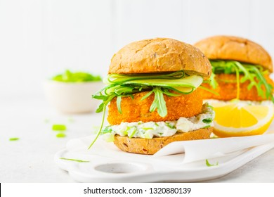Fish burger with cucumber, arugula and mayonnaise sauce, white background, vegetarian food.