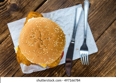 Fish Burger on wooden background (close-up shot; selective focus)