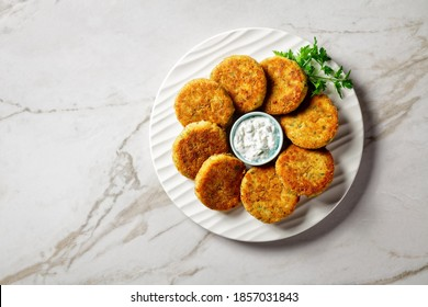 Fish cakes of cod or haddock fillet with potato and parsley, breaded in breadcrumbs on a white plate with tartar sauce in a gravy boat on a light marble stone background,  top view, close-up