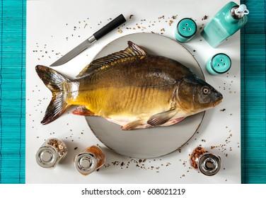 Fish carp. Fresh carp on the tray knife seasoning bottle of oil white background