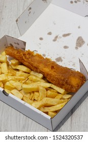 Fish and chips in a cardboard box from a takeaway.  Recycling packing.  Grey wood background