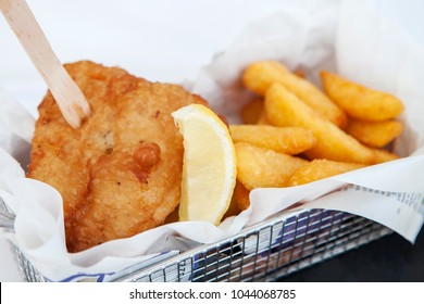 Fish and chips, with a chip fork and a lemon wedge in a metal basket