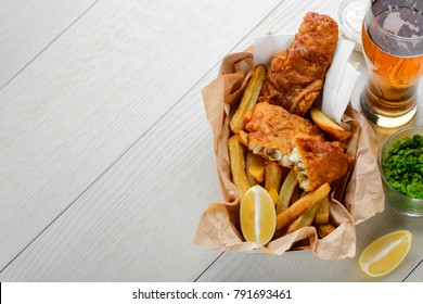 Fish and chips with lemon served in paper wrapper. Mashed green peas, salad and glass of beer. Favorite recipe for dinner.